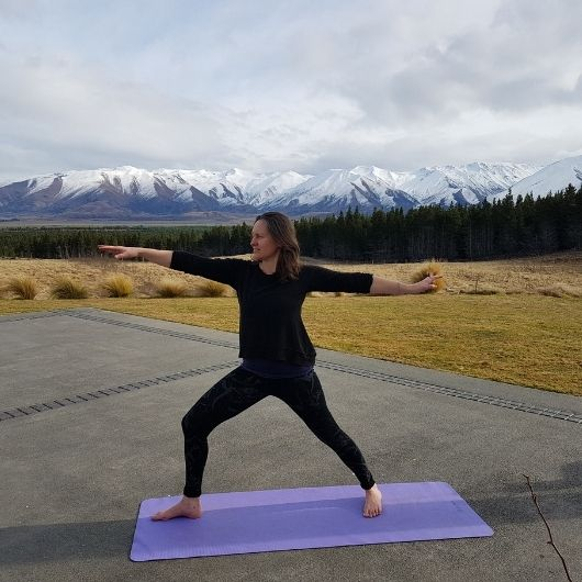 YOga teacher on patio with mountains in the background
